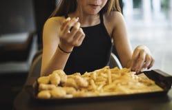 Ciérrese para arriba del adolescente que come las patatas fritas Fotografía de archivo libre de regalías