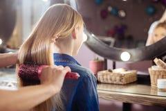 Ciérrese para arriba del adolescente que hace su pelo cepillar Fotografía de archivo