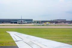 Ciérrese para arriba del ala del aeroplano en mantenimiento que espera del aeroplano para en el fondo del aeropuerto fotografía de archivo