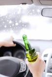 Ciérrese para arriba del alcohol de consumición del hombre mientras que conduce el coche Imagenes de archivo