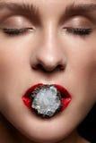 Ciérrese para arriba del anillo del bijouterie con la piedra en labios femeninos rojos de la boca Imagen de archivo libre de regalías