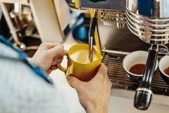 Ciérrese para arriba del barista que cuece la leche al vapor en la jarra con la máquina del café foto de archivo