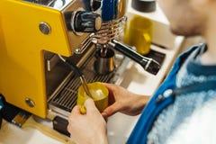 Ciérrese para arriba del barista que cuece la leche al vapor en la jarra con la máquina del café fotos de archivo libres de regalías