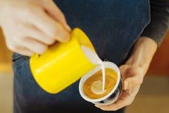 Ciérrese para arriba del barista que vierte la leche cocida al vapor en la taza de café que hace arte del latte foto de archivo