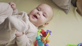 Ci?rrese para arriba del beb? luying en cama y que sonr?e en la c?mara Concepto de la ni?ez almacen de metraje de vídeo