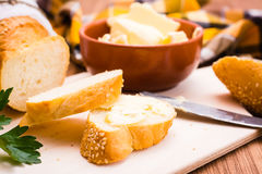 Ciérrese para arriba del bocadillo con mantequilla y el baguette cortado en una tabla de cortar Foto de archivo libre de regalías
