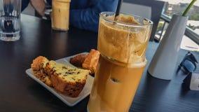 Ciérrese para arriba del café de Nescafe del hielo en taza de cristal única con la paja negra y las galletas frescas con el choco fotografía de archivo libre de regalías