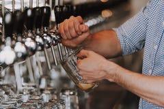 Ciérrese para arriba del camarero Pouring Lager Beer en golpecito imagenes de archivo