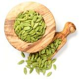 Ciérrese para arriba del cardamomo secado en el mortero de madera verde oliva, aislado en blanco fotografía de archivo libre de regalías