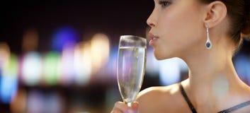 Ciérrese para arriba del champán de consumición de la mujer en el partido fotografía de archivo