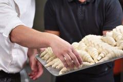 Ciérrese para arriba del chef de repostería que muestra una bandeja de pasta cruda fresca de los cruasanes fotos de archivo libres de regalías