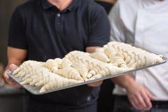 Ciérrese para arriba del chef de repostería que muestra una bandeja de pasta cruda fresca de los cruasanes imagen de archivo