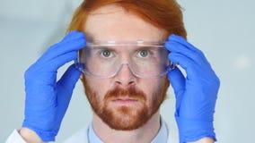 Ciérrese para arriba del científico de Reseach del pelirrojo, el doctor Wearing Protective Glasses Foto de archivo libre de regalías