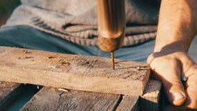 Ciérrese para arriba del clavo masculino del hierro de los martillos del carpintero en un tablón de madera almacen de video