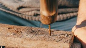 Ciérrese para arriba del clavo masculino del hierro de los martillos del carpintero en un tablón de madera metrajes