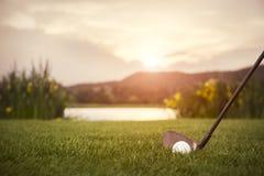 Ciérrese para arriba del club de golf en la puesta del sol fotos de archivo