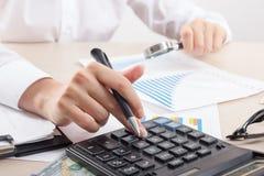 Ciérrese para arriba del contable o del banquero femenino que hace cálculos Ahorros, finanzas y concepto de la economía foto de archivo libre de regalías