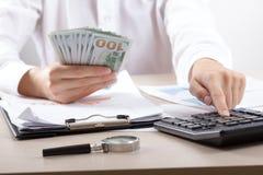 Ciérrese para arriba del contable o del banquero femenino que hace cálculos Ahorros, finanzas y concepto de la economía imagen de archivo