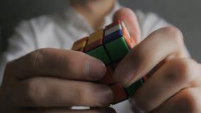 Ciérrese para arriba del cubo del ` s de Rubik en las manos de un hombre metrajes