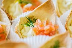 Ciérrese para arriba del cucurucho de la pasta con el relleno de color salmón de los pescados Imagen de archivo