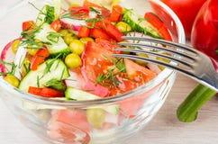 Ciérrese para arriba del cuenco transparente con la ensalada y la bifurcación vegetales Fotografía de archivo