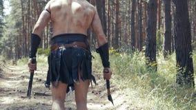 Ciérrese para arriba del cuerpo de un guerrero bárbaro con dos hachas en manos en un bosque metrajes