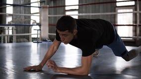 Ciérrese para arriba del deportista muscular joven que hace pectorales - de codos a las manos extendidas - mientras que se resuel metrajes