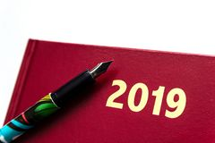 Ciérrese para arriba del diario de cuero rojo 2019 con la pluma en el fondo blanco fotos de archivo libres de regalías