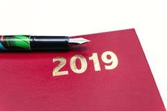 Ciérrese para arriba del diario de cuero rojo 2019 con la pluma en el fondo blanco fotografía de archivo