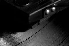 Ciérrese para arriba del disco de vinilo que juega en B&W Imagen de archivo libre de regalías