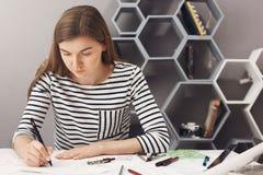 Ciérrese para arriba del diseñador joven hermoso concentrado los jóvenes que se sienta en la tabla en sitio ligero, haciendo para imagen de archivo