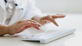 Ciérrese para arriba del doctor de sexo femenino que mecanografía en el teclado en la oficina almacen de video