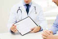 Ciérrese para arriba del doctor y del paciente masculinos con el tablero imágenes de archivo libres de regalías