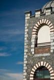 Ciérrese para arriba del edificio del detalle con las ventanas del arco en cielo azul Fotografía de archivo libre de regalías