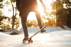 Ciérrese para arriba del entrenamiento masculino joven del skater en parque del patín Fotografía de archivo libre de regalías