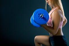 Ciérrese para arriba del entrenamiento del retrato de la mujer joven con pesa de gimnasia contra fondo oscuro fotografía de archivo