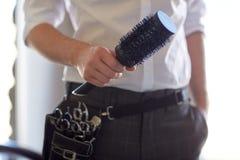 Ciérrese para arriba del estilista de sexo masculino con el cepillo en el salón Fotos de archivo libres de regalías