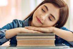 Ciérrese para arriba del estudiante adolescente que duerme en la pila de libros Imagen de archivo