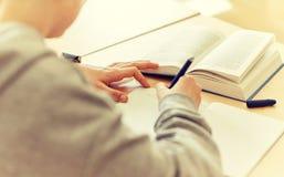 Ciérrese para arriba del estudiante que escribe al cuaderno en la escuela Foto de archivo libre de regalías