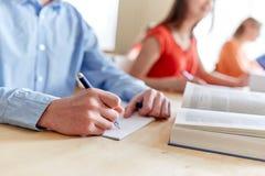 Ciérrese para arriba del estudiante que escribe al cuaderno en la escuela Foto de archivo
