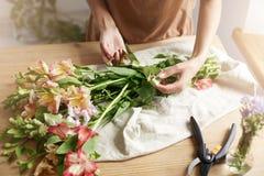 Ciérrese para arriba del florista de sexo femenino joven que ata la cinta en ramo en el lugar de trabajo fotos de archivo libres de regalías