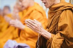 Ciérrese para arriba del foco de rogación del monje tailandés a mano con la cuerda blanca foto de archivo libre de regalías