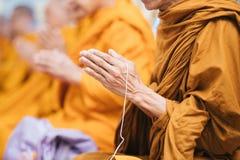 Ciérrese para arriba del foco de rogación del monje tailandés a mano con la cuerda blanca fotos de archivo libres de regalías