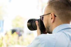 Ciérrese para arriba del fotógrafo de sexo masculino con la cámara digital Fotos de archivo