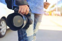 Ciérrese para arriba del fotógrafo que sostiene la cámara en sus manos, concepto de DSLR de las vacaciones de la forma de vida de imagen de archivo