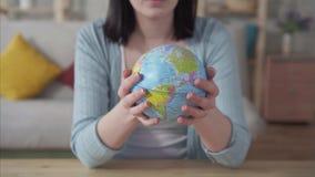 Ciérrese para arriba del globo de la escuela en las manos de una mujer joven, concepto de Día de la Tierra almacen de video