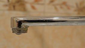 Ciérrese para arriba del goteo del agua de un golpecito en un cuarto de baño almacen de metraje de vídeo