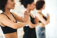 Ciérrese para arriba del grupo multicultural de mujeres que practican yoga imagenes de archivo