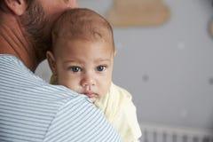 Ciérrese para arriba del hijo de Comforting Newborn Baby del padre en cuarto de niños Fotografía de archivo