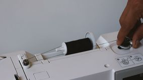 Ciérrese para arriba del hilo de la bobina de la mano del hombre en bobina de la máquina de coser almacen de metraje de vídeo